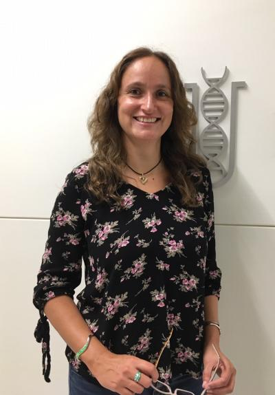 Dr. Ana Alonso standing in front of BDI sign/symbol (DNA helix inside test tube)