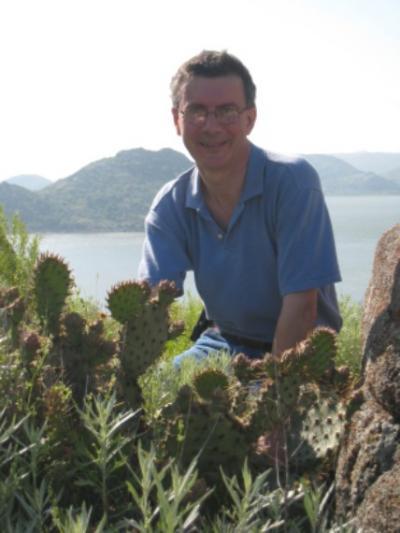 Richard Dixon sitting in cactus smiling
